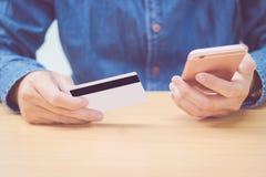 Mann, der Kreditkarte unter Verwendung des Handys hält Lizenzfreies Stockfoto