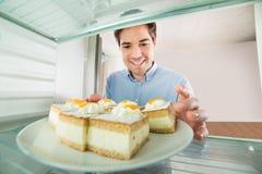 Mann, der Kuchen-Innenansicht den Kühlschrank nimmt Lizenzfreie Stockbilder
