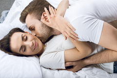 Mann, der lächelnde Frau im Bett küsst lizenzfreie stockfotografie