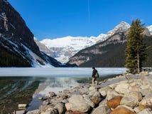 Mann, der Lake Louise und Berge ansieht stockbild