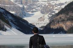 Mann, der Lake Louise und Berge ansieht Stockfoto