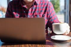 Mann, der an Laptop beim Trinken des Kaffees arbeitet Stockfotos