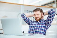 Mann, der Laptop-Computer in der Kaffeestube verwendet Stockfotos