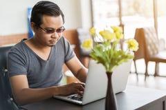 Mann, der Laptop-Computer im Café verwendet Lizenzfreie Stockfotos