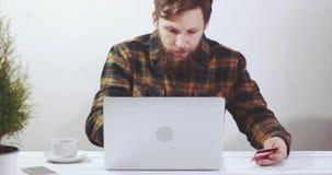 Mann, der Laptop-Computer on-line-Einkaufen mit Kreditkarte verwendet stock footage