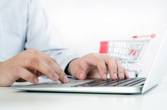 Mann, der Laptop für das Internet-Einkaufen verwendet Zusammensetzung mit Einkaufslaufkatze Stockfotografie