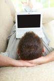 Mann, der Laptop im Haus verwendet Stockbild