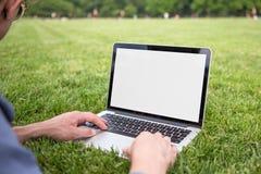 Mann, der Laptop im Parksommer verwendet Stockfotos
