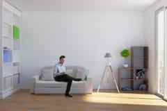 Mann, der Laptop im Wohnzimmer verwendet Stockbilder