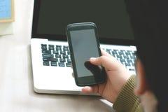 Mann, der Laptop und Mobile verwendet lizenzfreies stockbild