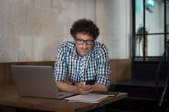 Mann, der Laptop und Smartphone am Café verwendet stockfotos
