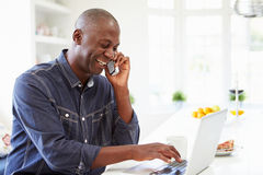 Mann, der Laptop verwendet und zu Hause am Telefon in der Küche spricht