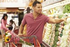 Mann, der Laufkatze durch Erzeugnis-Zähler im Supermarkt drückt Stockbilder