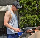 Mann, der Lebensmittel auf BBQ-Grill grillt lizenzfreies stockbild