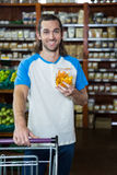 Mann, der Lebensmittelgeschäfteinzelteil mit Einkaufslaufkatze hält Stockfoto