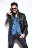 Mann in der Lederjacke und in der Sonnenbrille seinen Finger zeigend Stockfotografie