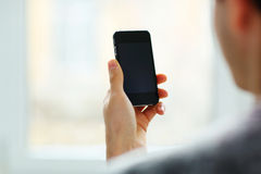 Mann, der leere Smartphoneanzeige betrachtet Lizenzfreie Stockfotografie