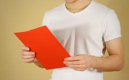 Mann, der leeres Papier des Rotes A4 liest Lesen Sie ausführliche Broschüre Broschüre p Stockbild