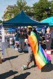 Mann, der LGBT-Flagge vor Hillary-Stand während Rockland-Stolzes trägt Lizenzfreies Stockfoto