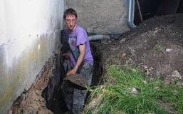 Mann, der Loch im Boden vorbereitet Stockbild