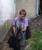 Mann, der Loch im Boden vorbereitet Stockfoto