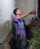 Mann, der Loch im Boden vorbereitet Stockbilder