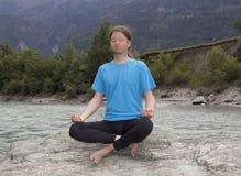 Mann, der in Lotus-Haltung sitzt und durch einen Fluss meditiert Lizenzfreie Stockfotos