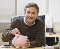 Mann, der Münze in Querneigung einsetzt stockfotografie