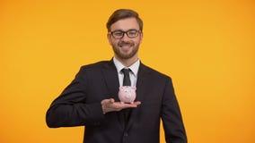 Mann, der Münze in Sparschwein, in Familienbudgetplanung, in Einsparungen und in Finanzierung einsetzt stock footage