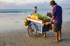 Mann, der Mais am Strand in Bali grillt Stockbilder