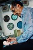 Mann, der Marionetten in seiner Werkstatt tut lizenzfreies stockbild