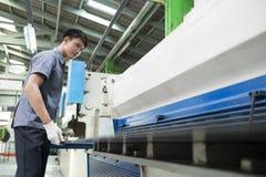 Mann, der Maschine der hydraulischen Presse steuert Stockfotos