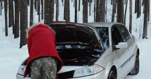 Mann, der Maschine des Autos betrachtet Mann, der gebrochenes Auto repariert Winter fahrend, Problem auf einer schneebedeckten La stock video footage