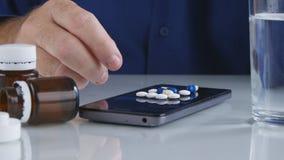Mann, der Medizin-Pillen von der Smartphone-Schirm-Oberfläche vorwählt lizenzfreie stockfotos