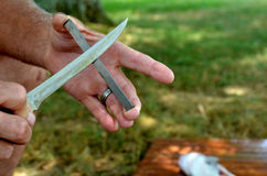Mann, der Messer auf Karbidblockstock schärft Stockfoto