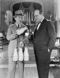 Mann, der Milch liefert und Schale für Geschäftsmann gießt (alle dargestellten Personen sind nicht längeres lebendes und kein Zus Lizenzfreie Stockbilder