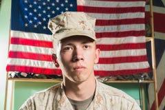 Mann in der Militäruniform auf USA-Flaggenhintergrund Stockfotografie