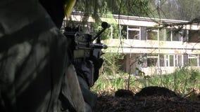 Mann in der Militäruniform mit einer Waffe versteckt sich unter Baum stock footage