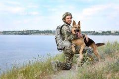 Mann in der Militäruniform mit Schäferhund verfolgen draußen Stockfoto