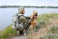 Mann in der Militäruniform mit Schäferhund verfolgen draußen Stockbild