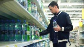 Mann, der Mineralwasser im Supermarkt kauft stock footage