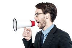 Mann, der mit Ärger über Megafon schreit Lizenzfreie Stockfotos