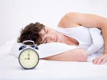 Mann, der mit Alarmuhr schläft Stockbild