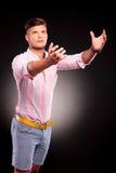 Mann, der mit beiden Händen erreicht Stockfotografie