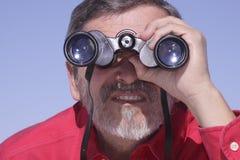 Mann, der mit Binokeln sucht Stockfotos