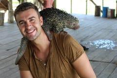Mann, der mit brasilianischem Stachelschwein spielt lizenzfreies stockbild