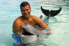 Mann, der mit Delphin spielt stockbild