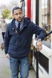 Mann, der mit dem Arm auf Geländer wartet Lizenzfreie Stockfotos