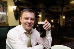 Mann, der mit dem dunklen Bierkrug aufwirft Stockbild
