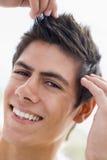Mann, der mit dem Haarlächeln spielt Stockfotos